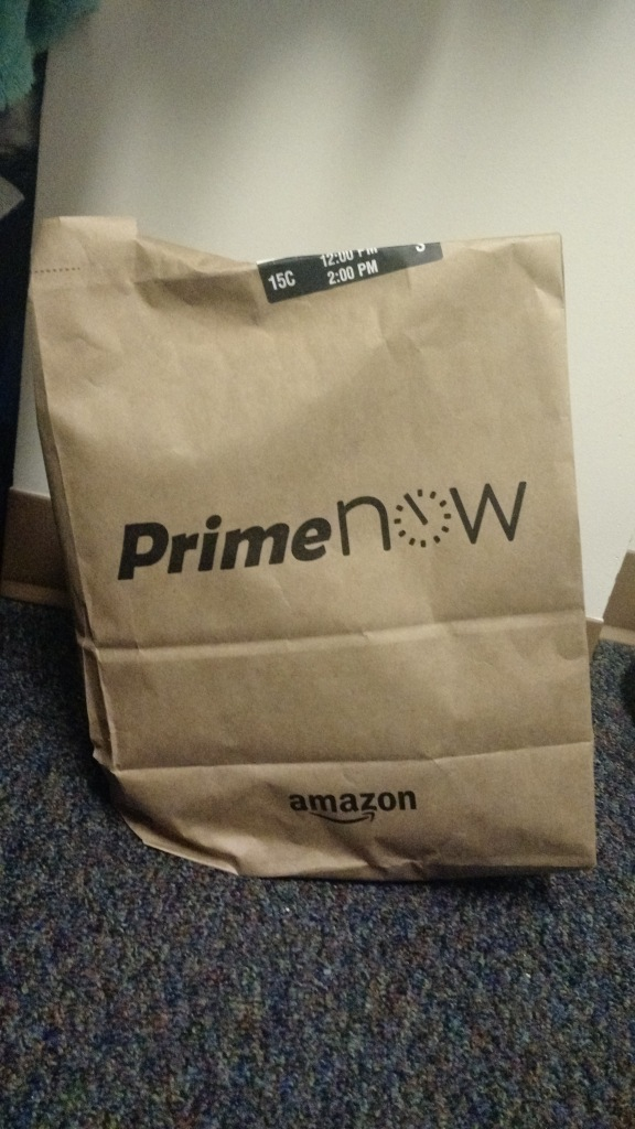 Brown bag with Amazon PrimeNow logo and items inside